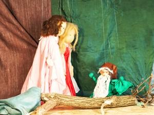 Der Zwerg bleibt an einem Baumstamm hängen, die Schwestern helfen ihm.